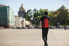 Tylny widok młodego eleganckiego mężczyzna turystyczny odprowadzenie przy pałac kwadratem blisko świętego Isaac ` s katedry w Pet fotografia stock