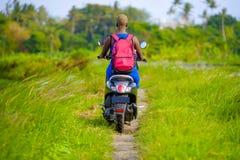 Tylny widok młodej turystycznej afro Amerykańskiej murzynki jeździecki motocykl szczęśliwy w pięknej Azja wsi wzdłuż zielonych ry Zdjęcia Royalty Free