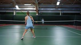 Tylny widok młody żeńskiej atlety doskakiwanie w rekreacyjnym terenie bawić się sport grę Trzy szczęśliwego dziecka ma tenisa zbiory