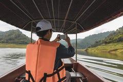 Tylny widok młody Azjatycki podróżnika mężczyzny obsiadanie na łodzi przeciw scenicznemu halnemu tłu Styl życia i podróży pojęcie fotografia royalty free