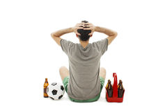 Tylny widok młody człowiek z piłki nożnej piłką i paczką piwny dopatrywanie mecz futbolowy, spojrzenie rozczarowywający odosobnio Obrazy Royalty Free