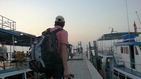 Tylny widok młody człowiek z plecaka i walizki odprowadzeniem wzdłuż mola Podróżować wybrzeże na wakacje zbiory wideo
