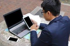 Tylny widok młody przystojny biznesmen używa pastylkę i laptop dla jego pracy na marmurze przy społeczeństwem outdoors parkuje obrazy stock