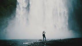 Tylny widok młody przystojny mężczyzna stoi blisko potężnej Gljufrabui siklawy w Iceland i bierze fotografie na smartphone zbiory