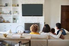 Tylny widok młody rodzinny obsiadanie na kanapie i dopatrywanie TV wpólnie w ich żywym pokoju zdjęcia stock