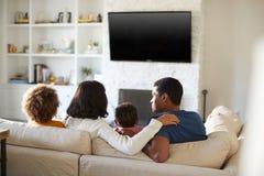 Tylny widok młody rodzinny obsiadanie na kanapie i dopatrywanie TV wpólnie w ich żywym pokoju, zakończenie w górę fotografia stock
