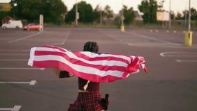 Tylny widok młody szczęśliwy amerykański dziewczyna bieg podczas gdy trzymający flaga amerykańską Wtedy obraca wokoło i spojrzeni zdjęcie wideo