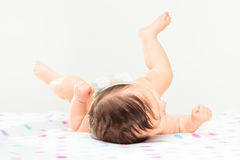 Tylny widok mały dziewczynki lying on the beach na polek kropkach powszechnych Obrazy Royalty Free
