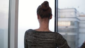 Tylny widok otwiera jej sypialni zasłony i outside w slowmotion młoda kobieta nadokiennego i przyglądającego zdjęcie wideo