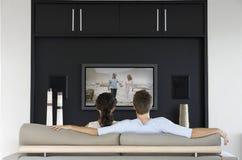 Tylny widok pary dopatrywania film na telewizi w żywym pokoju fotografia stock