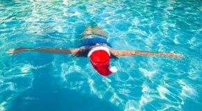Tylny widok piękna kobieta w Santa kapeluszu na błękicie Zdjęcie Stock