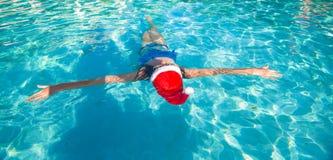 Tylny widok piękna kobieta w Santa kapeluszu na błękicie Zdjęcie Royalty Free