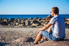 Tylny widok pije piwo na kamienistej plaży mężczyzna zdjęcie stock