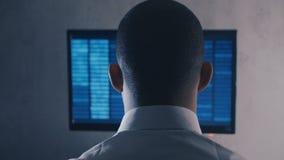 Tylny widok programisty programowania fachowy kod na komputerowym monitorze przy nocy biurem zdjęcie wideo