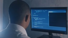 Tylny widok programisty programowania fachowy kod na komputerowym monitorze przy nocy biurem zbiory