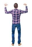 Tylny widok przystojny mężczyzna w w kratkę koszulowym utrzymaniu na brzęczeniach Fotografia Stock