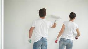 Tylny widok Robi mieszkanie naprawie Wpólnie Radosna para Młoda żona i mąż Malujemy ścianę z Białą farbą zdjęcie wideo