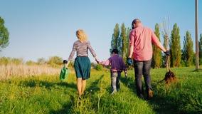 Tylny widok: Rodzina rolnicy z małym synem iść wpólnie zasadzać drzewa Znosi jabłoni rozsady, łopata i zbiory wideo