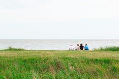 Tylny widok rodzinny obsiadanie na Minsmere plaży w UK zdjęcie royalty free