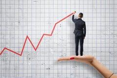 Tylny widok rysuje czerwień diagrama pozycję na woman& x27 biznesmen; s ręka Obrazy Stock