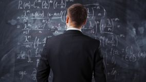 Tylny widok samiec przeciw kredowej desce z mathematics równaniami zbiory wideo