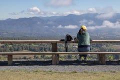 Tylny widok samotnie młoda kobieta jest usytuowanym na długiej drewnianej ławce i patrzeje tło góry i niebieskiego nieba fotografia stock