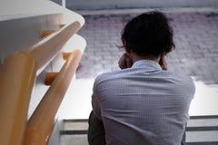 Tylny widok sfrustowany zaakcentowany młody Azjatycki biznesowego mężczyzna uczucie próbujący lub wyczerpujący przy schody biuro zdjęcie stock