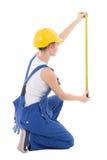 Tylny widok siedzący kobieta budowniczy mierzy coś z meas Zdjęcie Royalty Free
