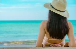 Tylny widok szczęśliwa młoda Azjatycka kobieta w różowym swimsuit i słomiany kapelusz relaksujemy wakacje i cieszymy się przy tro zdjęcie stock