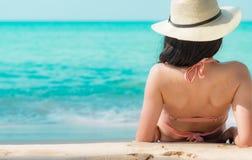 Tylny widok szczęśliwa młoda Azjatycka kobieta w różowym swimsuit i słomiany kapelusz relaksujemy wakacje i cieszymy się przy tro obraz stock