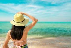 Tylny widok szczęśliwa młoda Azjatycka kobieta z słomianym kapeluszem relaksuje wakacje i cieszy się przy tropikalną raj plażą Dz zdjęcia royalty free