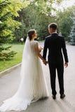 Tylny widok szczęśliwa para państwa młodzi odprowadzenie w parku Tylni widok nowożeńcy spojrzenie przy each inny przy ślubem wewn zdjęcie royalty free