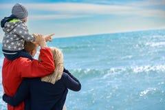Tylny widok szczęśliwa rodzina przy tropikalną plażą na wakacje Zdjęcia Royalty Free