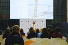 Tylny widok uczestnicy konwersatorium, szkolenie lub wykład w wielkiej widowni z dużym ekranem, zdjęcia stock