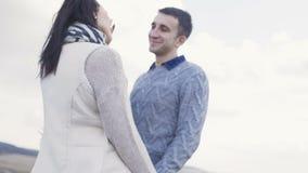 Tylny widok uroczy pary odprowadzenie przy skałą w wietrznym dniu 4K zbiory wideo
