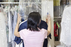 Tylny widok w połowie dorosły pracownika kładzenia klingeryt na suchym czyścić odziewa fotografia stock