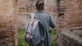 Tylny widok z podnieceniem młody żeńskiego ucznia badacz z plecaka i mapy rekonesansowymi antycznymi ruinami w Ostia, Włochy zbiory wideo