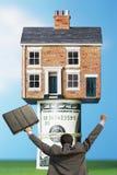 Tylny widok zwycięski biznesmen z teczką przed domem na pieniądze rolkach Obraz Stock