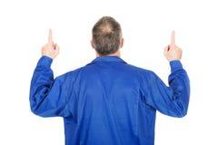 Tylny widoku repairman wskazuje up z oba rękami Fotografia Stock