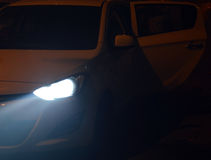 Tyndall effekt från billyktan för Xenon (vit) av en bil under natt Fotografering för Bildbyråer