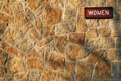 Tyndall Stone Wall Background. A woman sign on a tyndall stone building background. Tyndall Stone is a mottled dolomitic limestone, specific to the Selkirk Red Stock Photo
