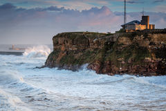Tynemouth Coast Guard Station and Stormy Sea. A stormy sea hits Tynemouth North Pier, resulting in high crashing waves cascading into the mouth of the River Tyne Stock Photo