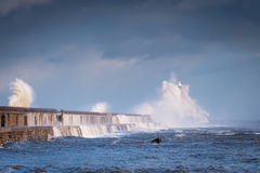 Tynemouth Lighthouse engulfed by Waves. A stormy sea hits Tynemouth North Pier, resulting in high crashing waves cascading into the mouth of the River Tyne Royalty Free Stock Photos
