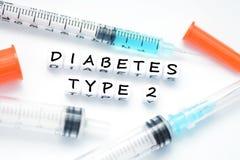 Typ - text för 2 sockersjuka som stavas med plast- bokstavspärlor som förläggas bredvid en insulininjektionsspruta Royaltyfria Bilder