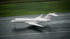 TypBombardier globala 5000 som för privat stråle landar på våt landningsbana på Royaltyfri Foto