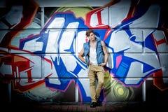 Type à la mode contre un mur avec le graffiti Photos libres de droits