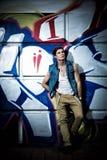 Type à la mode contre un mur avec le graffiti Photos stock