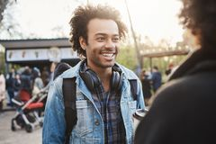 Type à la peau foncée avec du charme émotif avec la coupe de cheveux Afro et le sourire sincère parlant à son amie, décidant où a Images stock