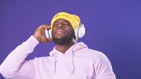 Type à la peau foncée heureux dans le hoodie et le chapeau jaune écoutant les voies préférées dans des écouteurs clips vidéos