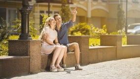 Type étreignant l'amie la date, montrant quelque chose en air, jeunes couples dans l'amour Image stock